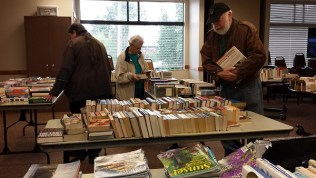 People browse the annual book sale for the Writers in the Grove.
