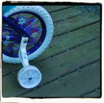Child bicycle with training wheels and flowers in the spokes