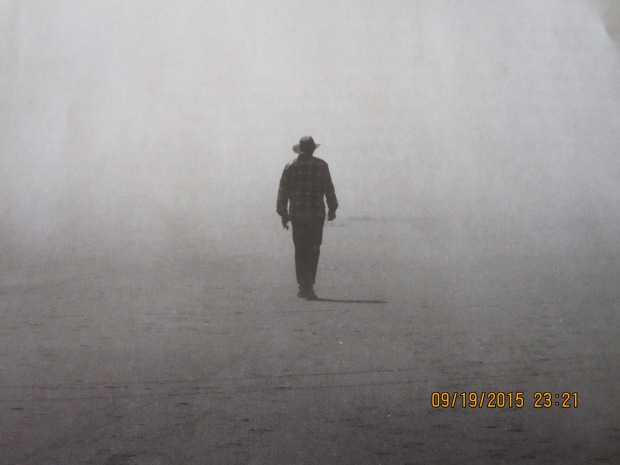 A photo from The Sun Magazine, a solitary form walking in the mist.